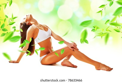Sexy woman siting on the floor with leaves