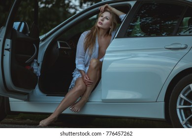 Sexy woman is sitting in a car, she is thinking and dreaming.