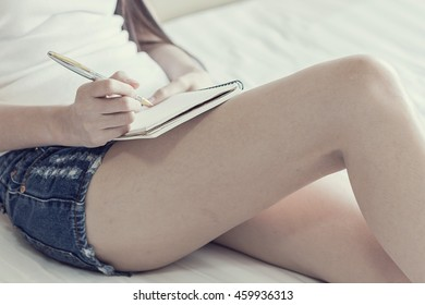 sexy woman sitting on her cozy bed and making notes to her diary, Low light, selective focus on hand, Vintage tone filter
