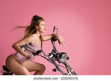 Sexy woman sitting on the motobike and enjoy the ride,dressed in sexy striped bodysuit. Lifestyle portrait bright toned colors,cool rock n roll girl,Enjoy ride in summer sunny hot days,red lips.
