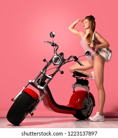 Sexy woman sitting on the motobike and enjoy the ride,dressed in sexy striped bodysuit. Lifestyle portrait bright colors,cool rock n roll girl, Standing near the bike and looking into the distance