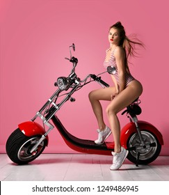 Sexy woman sitting on the motobike and enjoy the ride,dressed in sexy striped bodysuit. Lifestyle portrait bright toned colors,cool rock n roll girl, looking at the camera