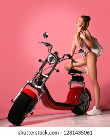 Sexy woman sitting on the motobike and enjoy the ride,dressed in sexy striped bodysuit. Over pink background