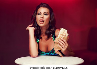 Sexy woman sitting at table in night club or bar and eating kebab or shaverma. Fashion style portrait