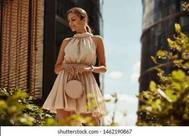 Sexy woman with small handbag wear summer dress