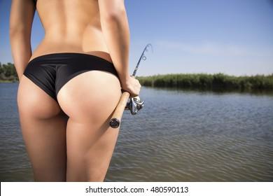 Sexy woman with spinning fishing. Fishing predator