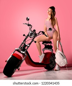 Sexy woman standing near the motobike, dressed in sexy striped bodysuit. Lifestyle portrait bright toned colors,cool rock n roll girl,Enjoy ride in summer sunny hot days,red lips,passion.