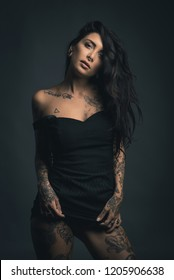 Sexy woman studio portrait with black dress and tattoos against dark background.