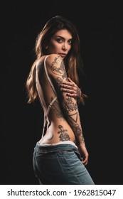 Sexy Frau Studioporträt mit weißer Dessous und Tätowierungen auf dunklem Hintergrund.