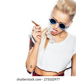 Sexy woman in sunglasses and white t-shirt blowing smoke from a cigar. Swag style girl. White background, not isolated
