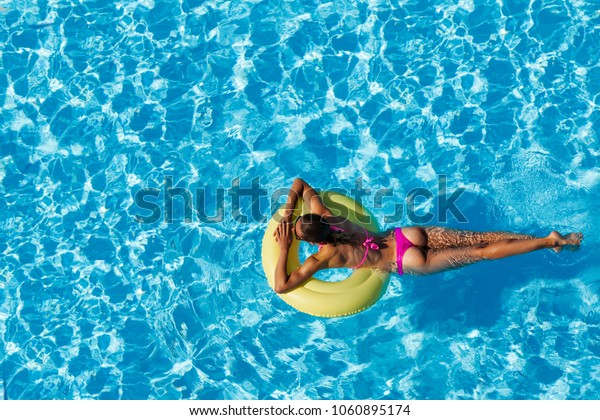 Sexy woman swimming on rubber ring in the pool