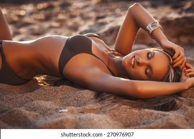 Sexy woman in a swimsuit relaxing on the sand of the beach. Tan skin