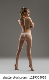 Sexy woman topless full-length rearview