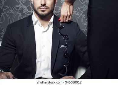 Sexy woman trying seduce rich businessman on sofa at night, bdsm