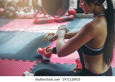 Sexy woman tying tape around her hand before get boxing gloves preparing to boxing practice.
