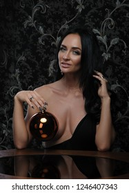 Sexy woman under table with new year ball in her hand