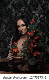 Sexy woman under table with new year christmas tree