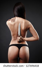 Sexy woman in underwear with her back to camera, hands up, in one hand holding a large knife behind her back.