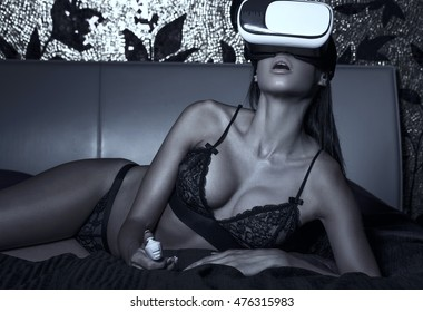 Sexy woman in underwear using VR glass in bed in dark, using remote control, virtual reality