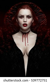 Sexy woman vampire in black dress with blood on neck