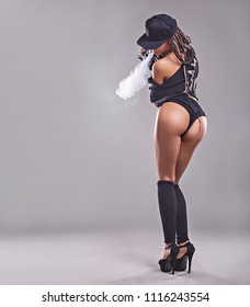Sexy woman is vaping. Studio shooting.Black background