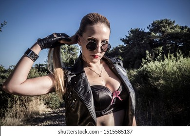 Sexy woman in vintage sunglasses and leather gloves. Gangsta girl with blue eyes and red lips.