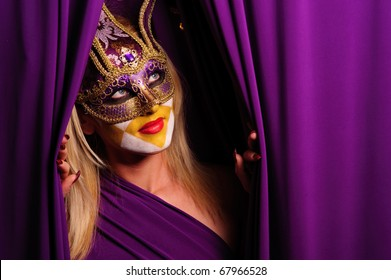 sexy woman in violet mask open curtain