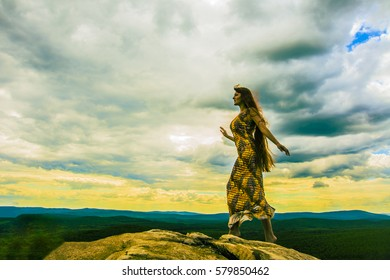 Sexy woman walk on the stone. Young redhead woman with long hair going on cliff's edge and looking at far away on forest and mountain background