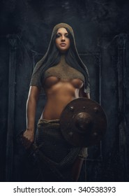 Sexy woman warrior in iron armor holds shield.