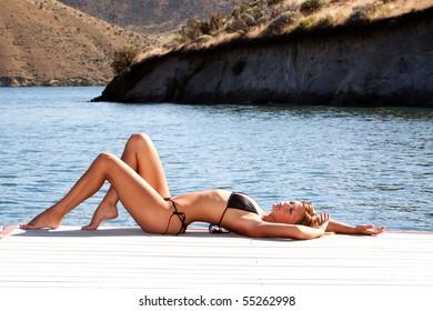 Sexy woman wearing a bikini by the lake