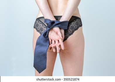 Sexy woman wearing chic black lingerie in bondage with her hands tied by a male necktie conceptual of a female sex symbol, closeup body view over grey