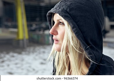 Sexy woman wearing a hooded cardigan outside in urban enviroment