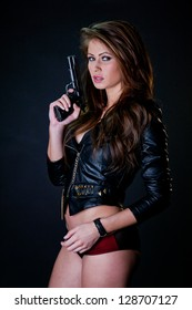 Sexy woman wearing jacket and lingerie holding gun against a black background