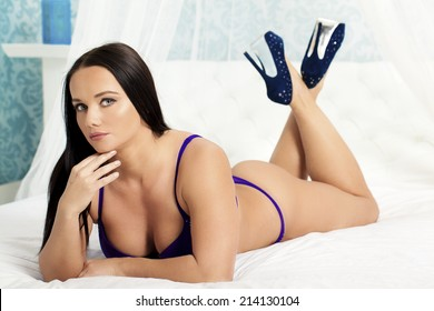 A sexy woman wearing lingerie and high heels relaxing on a bed.
