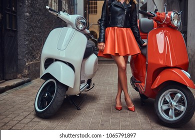 Sexy woman wearing stylish red skirt and leather jacket standing on an old narrow street with two classic Italian scooters.