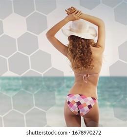 Femme sexy portant un chapeau de soleil et un bikini, profitant d'une journée à la plage