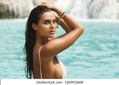 Sexy woman in white swimsuit is posing on the rock beside beautiful waterfall with blue water
