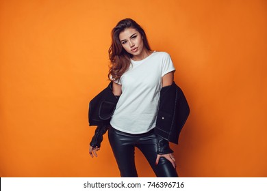 Sexy woman in white t-shirt and jacket on the orange background. Mock-up.