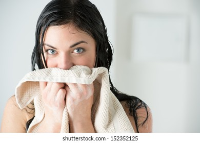 Sexy woman wiping herself with towel after taking shower at home and looking at camera