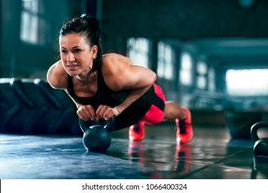 Sexy woman workout push ups on kettlebell at gym