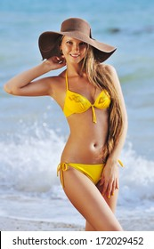 The sexy woman in yellow bikini and a hat having good time on a tropical beach