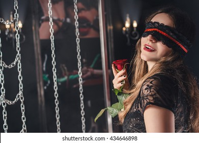 sexy woman, a young girl with a rose in the blindfold on a sado BDSM room, role play, women sexy lingerie, background chain, passionate mistress