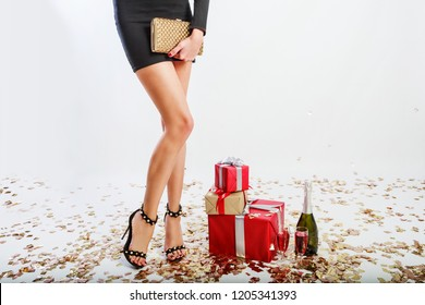 Sexy woman's legs on white  background, shining golden confetti, gift boxes, glasses of champagne. Celebrating time. Elegant purse with rhinestones.