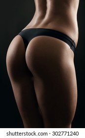 Sexy woman's sport buttocks in black lingerie close-up