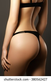 Sexy woman's sport buttocks in black lingerie close-up. Beautiful female body part. Sexy female buttocks. Beautiful female slim body.Beauty part of female body