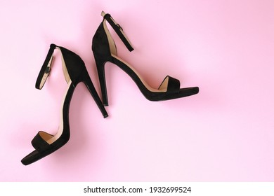 Sexy women black sandals with high-heeled stilettos on a pink background. Flat lay with copy space