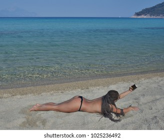 Sexy women taking selfie on a beautiful quiet sea beach with smartphone.