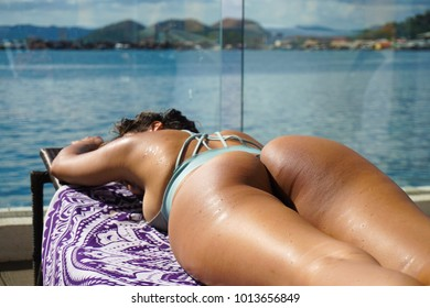 Sexy women tanning her booty poolside