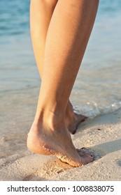 Sexy women's legs is on a beach