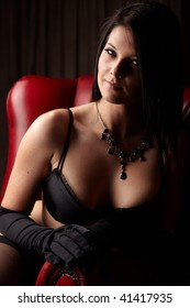 Sexy young adult caucasian woman in black lingerie with high contrast lighting